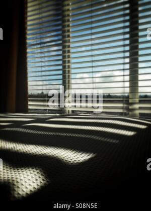 Window venetian blinds casting shadows on bed - Stock Photo