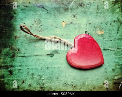Red wooden heart with a thread on grungy background - Stock Photo