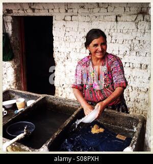 A maya indigenous woman washes a dish at pila (Guatemalan sink) in Guatemala. - Stock Photo