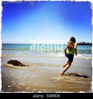 A ten year old girl runs on Seabright State Beach. Santa Cruz, California, USA - Stock Photo