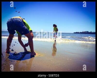 A ten year old and six year old brother and sister play at Seabright State Beach. Santa Cruz, California, USA - Stock Photo
