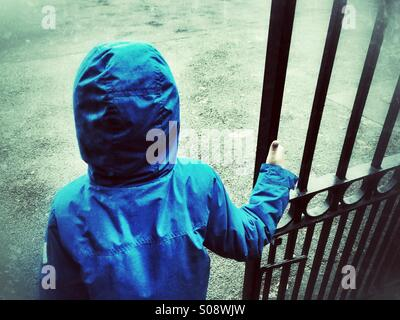 Little boy in blue coat waiting by the gate - Stock Photo