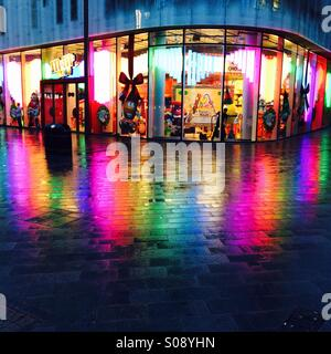 Colourful rainbow light reflection on ground in front of the M&Ms store in Leicester Square, Central London - Stock Photo