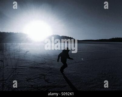 A boy running on ice during sunset - Stock Photo