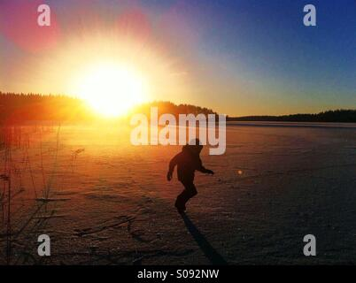 A boy running on ice of frozen lake in Kihniö, Finland - Stock Photo