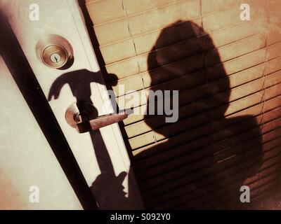 Shadow of a person in a hooded sweatshirt holding a hammer about to break into a home - Stock Photo