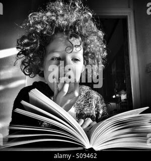 Girl eating an apple while reading a book. - Stock Photo