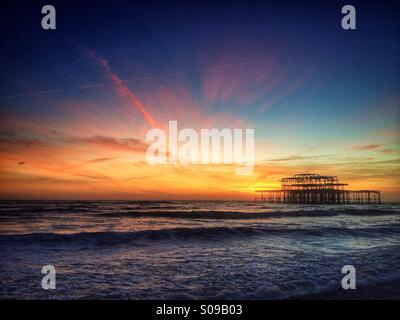 The burnt out remains of Brighton's West Pier at sunset, in Brighton, England, UK. - Stock Photo