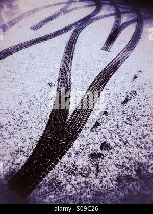 Tyre tracks forming a double heart shape on the snow covered road. - Stock Photo