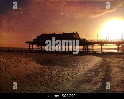 Atmospheric silhouette of Cleethorpes Pier at sunrise, architectural minimalism set against the rising sun, seen - Stock Photo