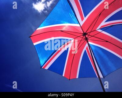 The sun shines through an umbrella with a design of the Union Flag of Great Britain, against a bright blue sky on - Stock Photo