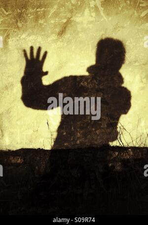 Stop! No more! Man casting a shadow on a wall expressing, Stop!, No more! - Stock Photo