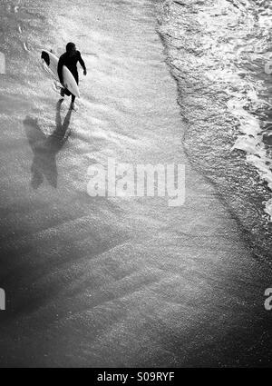 Surfer walks into the surf. Manhattan beach, California, USA. - Stock Photo