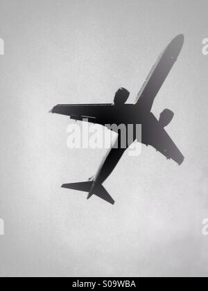 Low flying passenger aircraft coming in to land - Stock Photo
