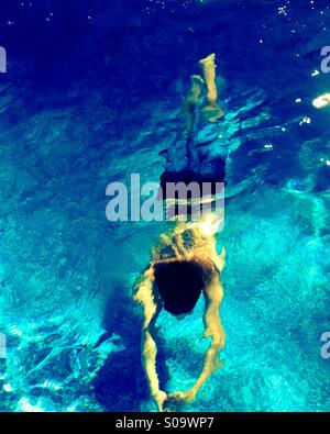 Young man swimming underwater in swimming pool as the sun glistens through the water. - Stock Photo