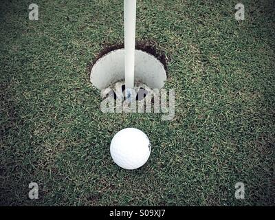 Golf ball near to hole - Stock Photo