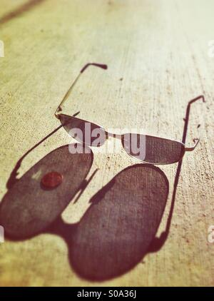 Sunglasses on the pavement casting long shadows - Stock Photo