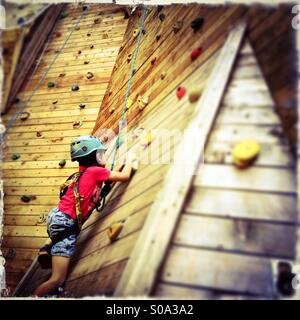 A six year old boy climbs a rock wall. - Stock Photo