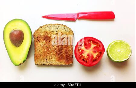 Making of a vegan/vegetarian open sandwich with avocado, tomato and whole wheat bread toast. - Stock Photo