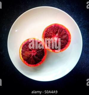 A vibrant red blood orange sliced in two on a white plate. - Stock Photo