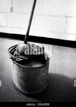 An old mop and metal bucket. - Stock Photo