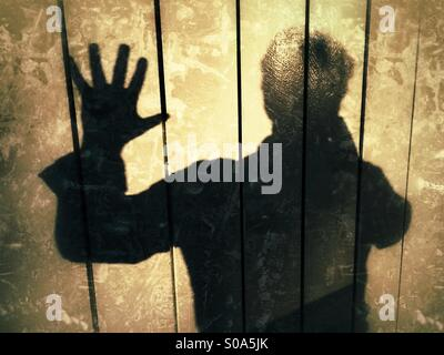 Man casting a shadow on a wall, Expressing, STOP!, no more! - Stock Photo