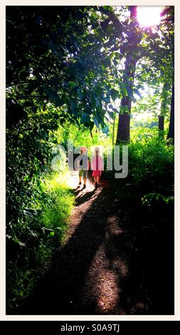 Two children walking on path in forrest - Stock Photo