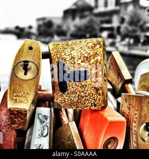 Golden padlock fastened with others by couples on a bridge - Stock Photo