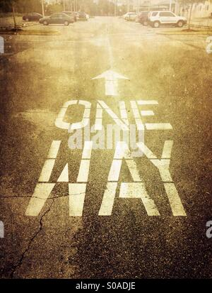 One way and an arrow painted on the asphalt in a parking lot. - Stock Photo