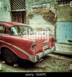 Rear view of a red vintage Cuban Car, parked by a peeling painted decaying exterior wall. Havana, Cuba, Caribbean - Stock Photo