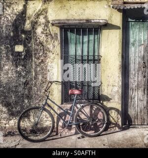 Bicycle leaning and casting a shadow against a grubby shuttered window walled property. Trinidad Sancti Spiritus - Stock Photo