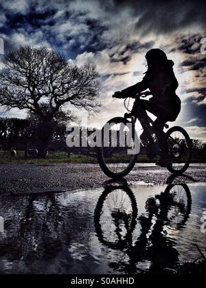 Young girl on bike in silhouette reflected in puddle - Stock Photo