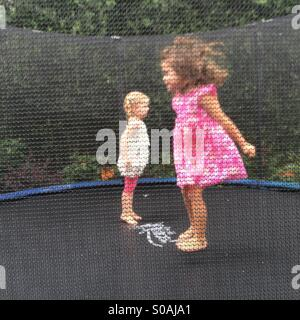 Two little girls jumps on a trampoline. - Stock Photo