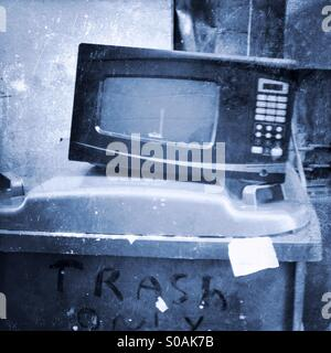 Microwave oven sitting on a trash can. - Stock Photo