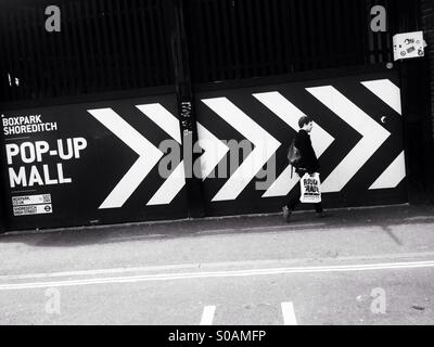 A man dressed in black carrying a white Rough Trade record shop bag walks past a large black and white chevron sign - Stock Photo