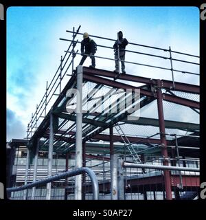 Builders putting up a scaffolding around a steel frame - Stock Photo