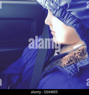 Profile of young boys face partially obscured by jacket hood - Stock Photo