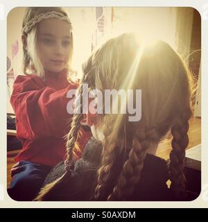 Mother and daughter making plaits in each other's hair in beautiful dreamy sunshine - Stock Photo