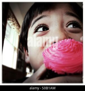 A six year old Asian Caucasian mixed race boy takes a bite of a cupcake. - Stock Photo