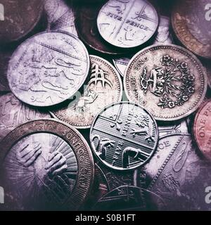 A background of British coins with grunge filters applied - Stock Photo