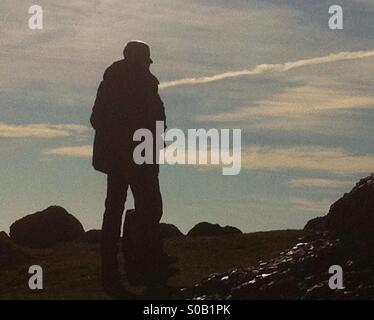 Man standing on rock overlooking Rhossili beach in the Gower peninsula - Stock Photo