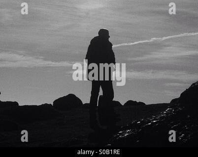Silhouette of a man standing on rock overlooking Rhossili beach in the Gower peninsula - Stock Photo