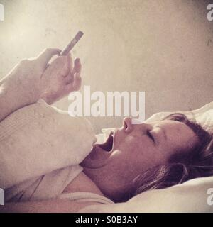 A yawning woman lying in bed using a mobile phone in bed - Stock Photo