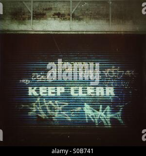 Garage door with 'Keep Clear' and graffiti painted on it. - Stock Photo