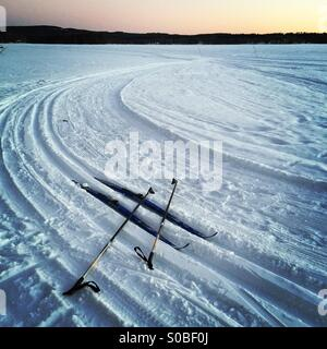 A pair of cross country skis and poles in the shape of a hashtag in some wilderness tracks on a frozen Nordic lake - Stock Photo