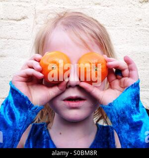 Child or children can have too much fruit! Girl holding two oranges over her eyes. - Stock Photo