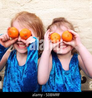 Children with orange eyes. Two sisters holding oranges over their eyes as a game, which could illustrate eating - Stock Photo