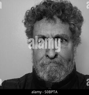 White man, age 64, with beard and expression of anger and frustration , close-up, Seattle, USA - Stock Photo