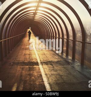 A silhouette of a man walking down a tunnel at sunrise in Glasgow - Stock Photo