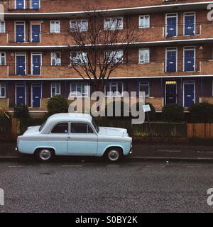 an old light blue car parked on the pavement in front of a block if flats in Eade rd, Hackney , London - Stock Photo